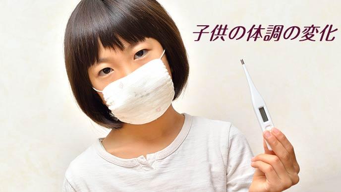 マスクして体温計を持つ子供
