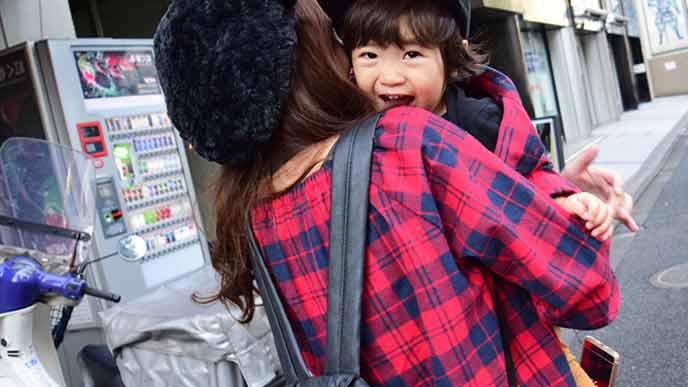 子供を抱っこして歩く母親