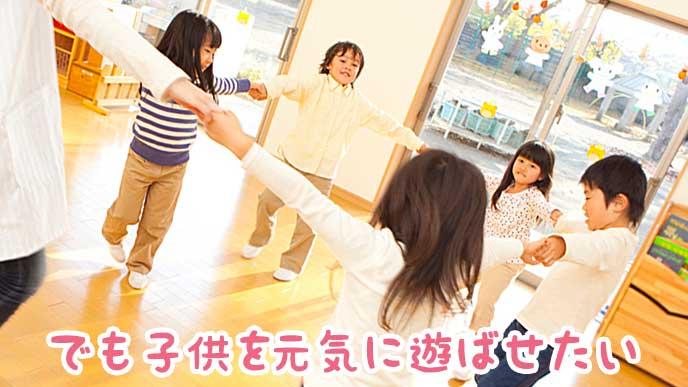 児童館の屋内で輪になって踊る子供達