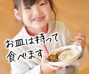 お皿を持って食事する子供