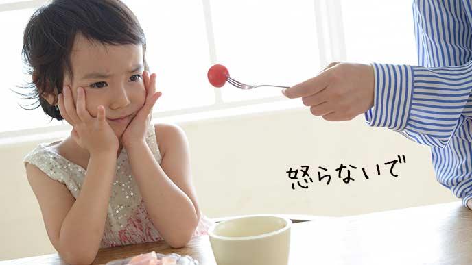 トマトを食べない子供にミニトマトを差し出す母親