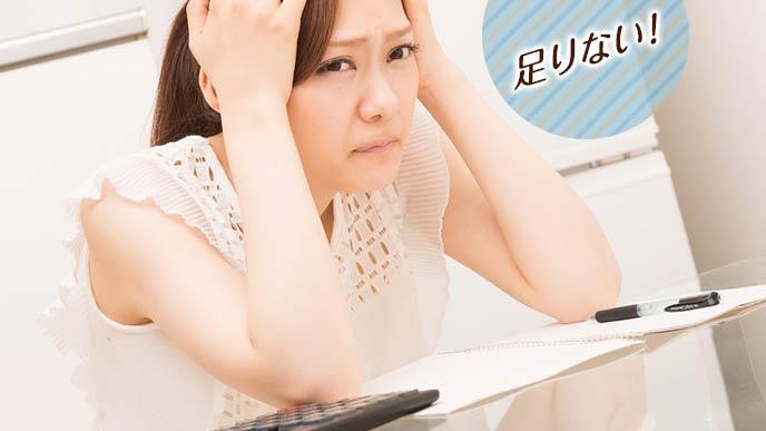 家計簿をつけながら頭を抱える主婦