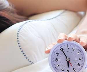 目覚まし時計に手を伸ばす女性