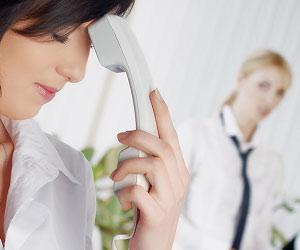 職場で電話連絡を受けて困る女性