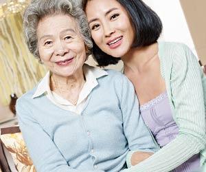 祖母と並んで笑顔の女性