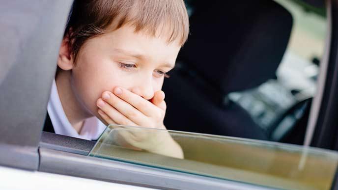 車の窓を開けて口を押える子供