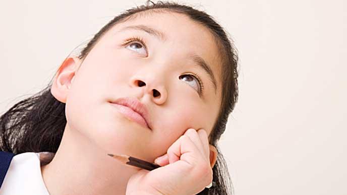 鉛筆を持って頬に片手をつき悩む女の子