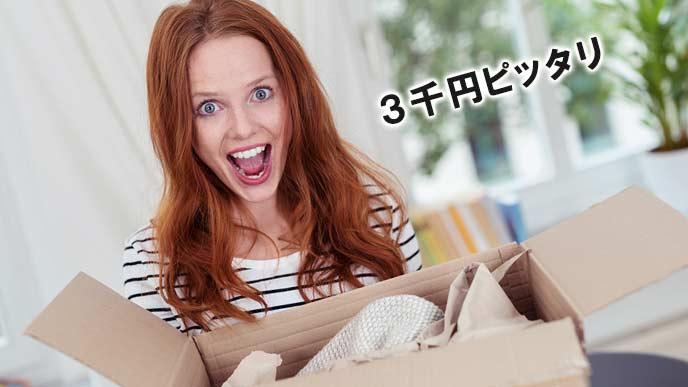 宅配された箱を開けて喜ぶ女性