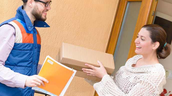 自宅で宅配の荷物を受け取る女性