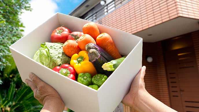 野菜の入った箱を宅配する男性の手