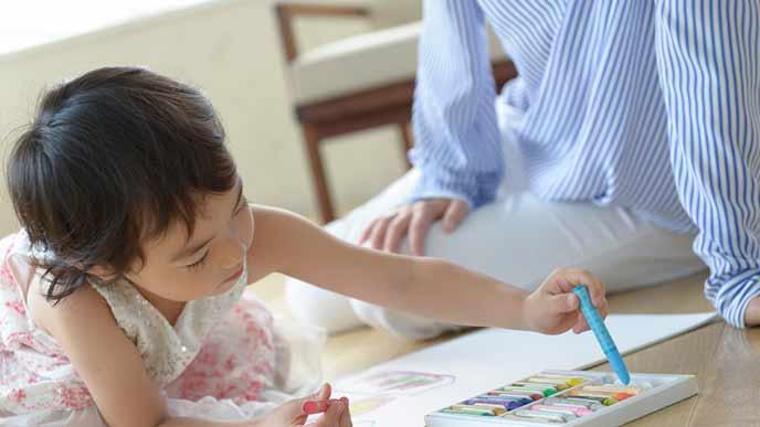 子供のお絵描きを見守る母親