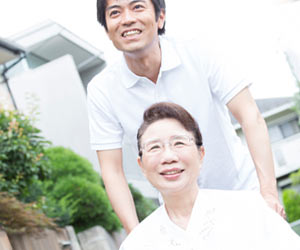 親を車椅子で散歩させる男性