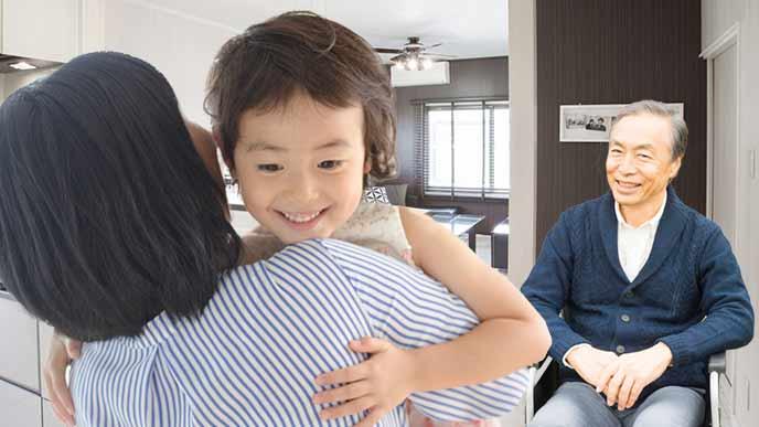 車椅子に座る父親を子供を抱っこしながら世話する女性