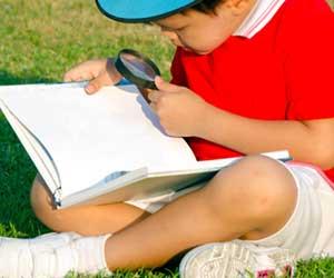 本を虫眼鏡で調べる子供