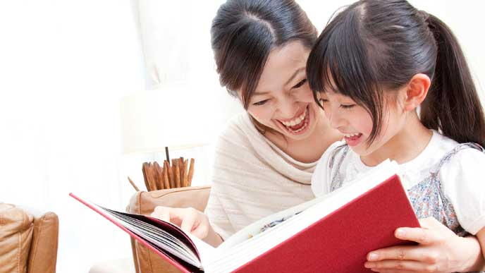 娘と一緒に本を読む母親