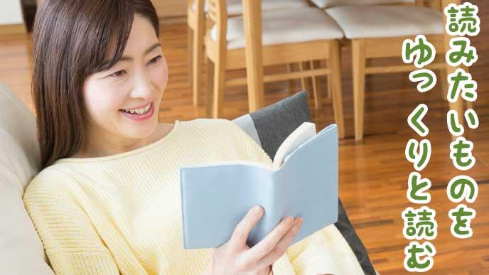 自宅のリビングで読書をしている主婦