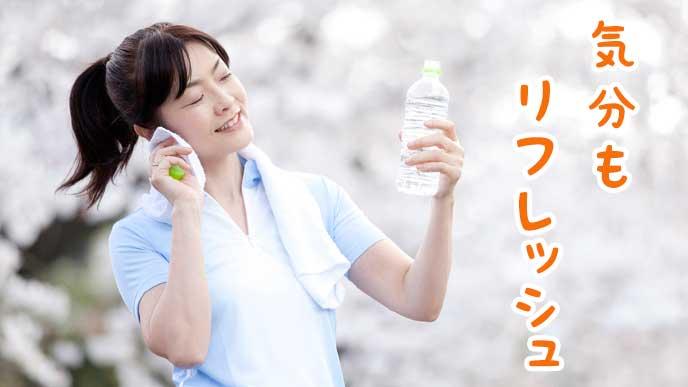 ランニングして汗を拭いている女性