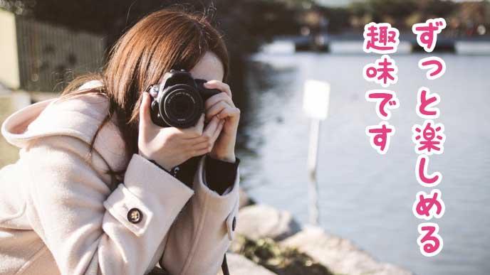 外でカメラを使って写真を撮る主婦