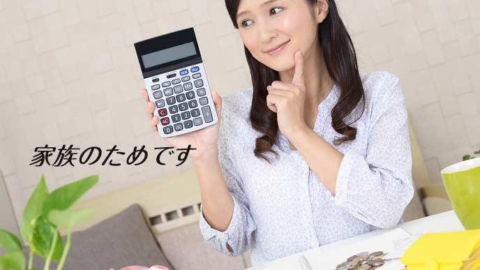 電卓持ってお金の計算する主婦