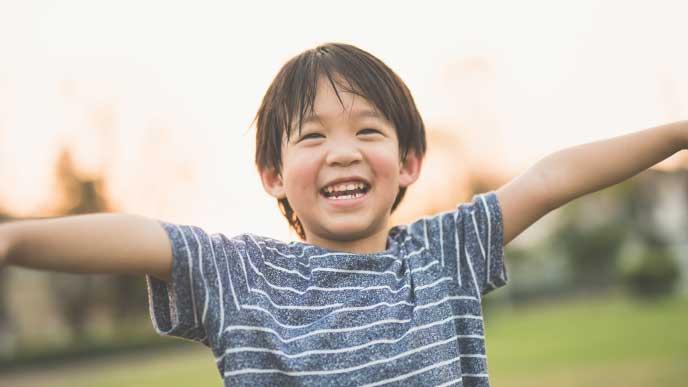 夕方の公園で腕を広げてニッコリ笑う男の子