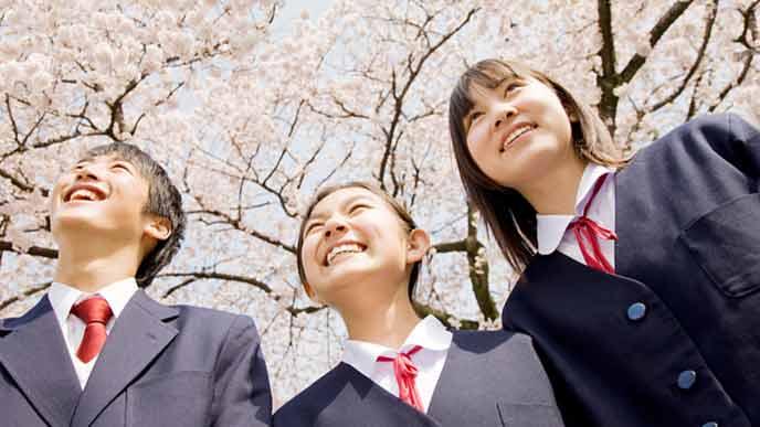 男女中学生が制服姿で桜の下に立つ