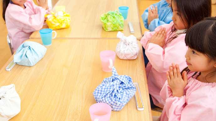 お昼のお弁当の時間で手を合わせる園児