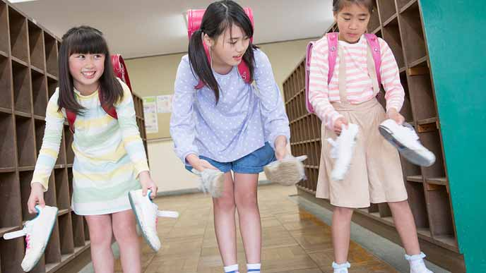 学校の玄関で靴を持つ小学生