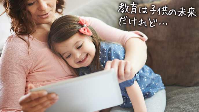 子供にタブレットを見せる母親