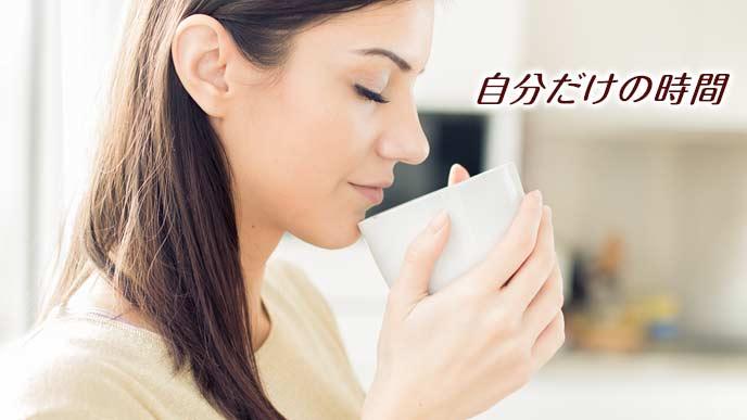 台所でコーヒーカップを両手で持って一息つく女性