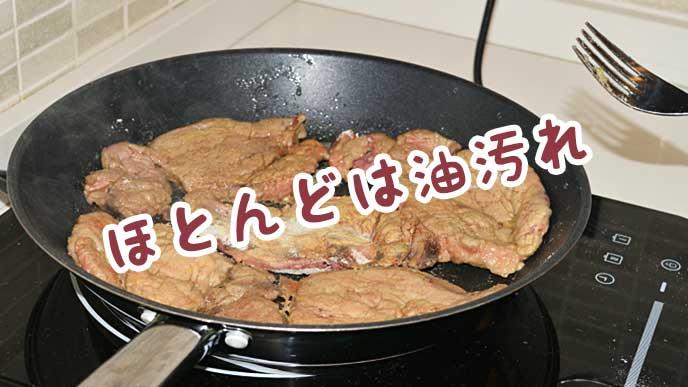 キッチンでフライパンを使って肉を調理する
