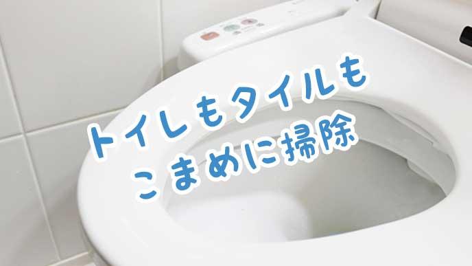 洋式のトイレと白いタイルの壁