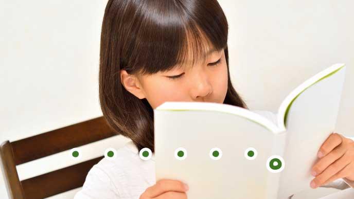 ムスっとした顔で本を読んで勉強する女の子