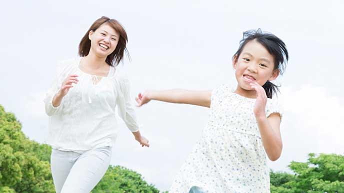 外で子供と一緒に走る母親