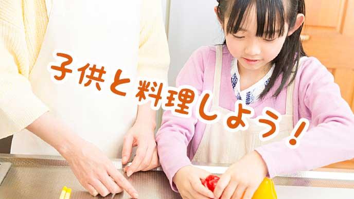 キッチンで母親と一緒に料理を作る女の子