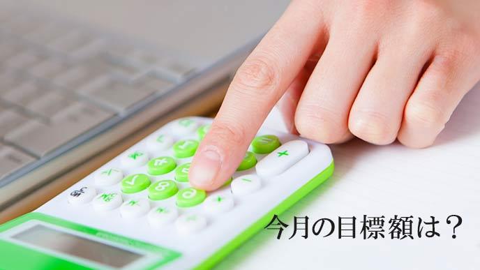 電卓でお金の計算をする女性