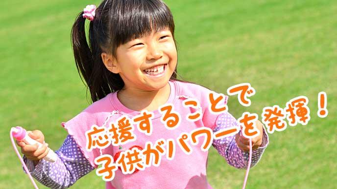 芝生の上で縄跳びをしている女の子