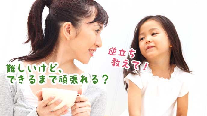 カップを持ちながら子供と会話している母親
