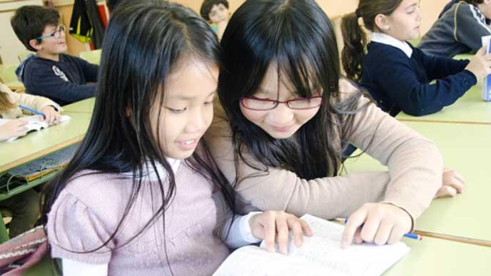 仲良く本を読んでいる女の子達
