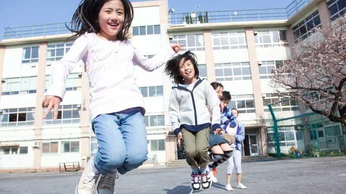 小学校の庭で縄跳びをしている子供達