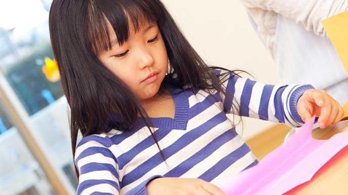 保育園で折り紙を折っている女の子