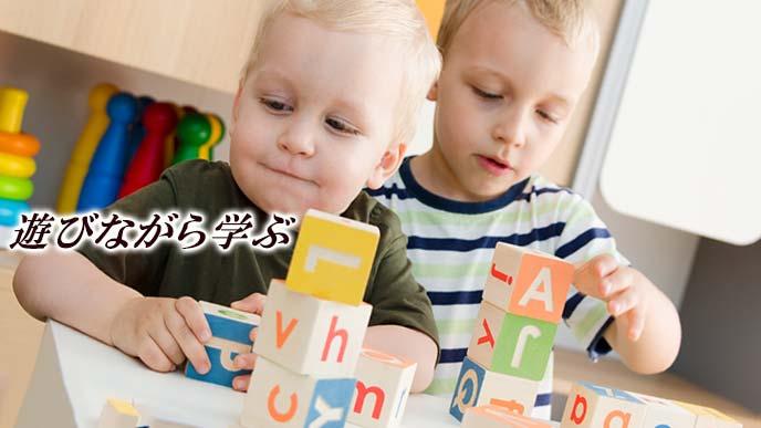 アルファベットの積み木で遊ぶ幼児