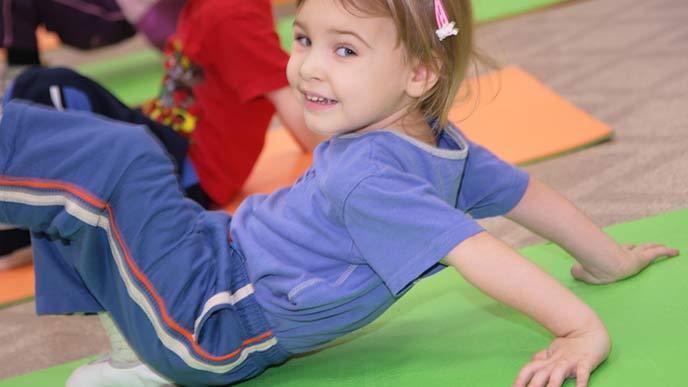 床で柔軟体操する幼児