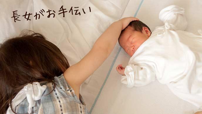 小学生のお姉さんが赤ん坊をあやしている