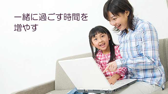 子供と一緒にラップトップを操作する母親