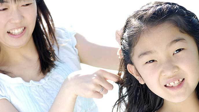 子供の髪の手入れをしてやる母親