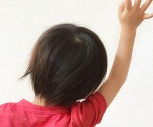 手を上げて友達に呼びかける子供