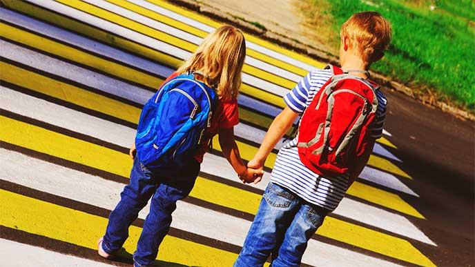 妹の手を繋いであげて一緒に横断歩道を渡ろうとしてるお兄ちゃん