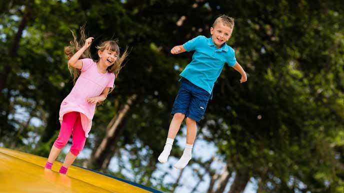 戸外のトランポリンでジャンプする子供達