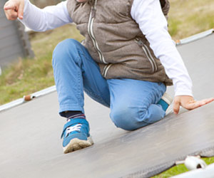 戸外のトランポリンに遊ぶ子供