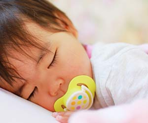 おしゃぶりを咥えて眠る幼児